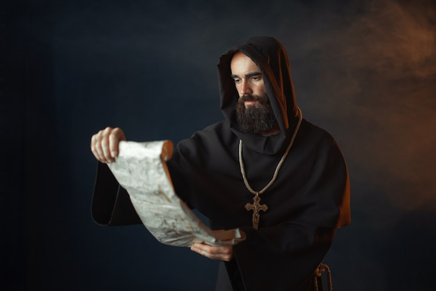 Middeleeuwse monnik met een boosaardig gezicht leest een gebed