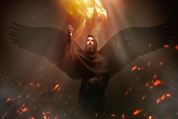 Middeleeuwse monnik met vleugels, religie. mysterieuze monnik die in donkere cape vliegt, mysterie en spiritualiteit