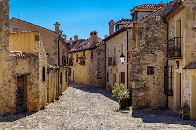 Middeleeuwse oude stad met stenen huizen, oude deuren en ramen, geplaveide straatjes en pittoreske sfeer. pedraza, segovia, spanje, europa.