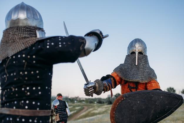 Middeleeuwse ridders in harnas en helmen vechten met zwaarden. gepantserde oude krijgers poseren in het veld