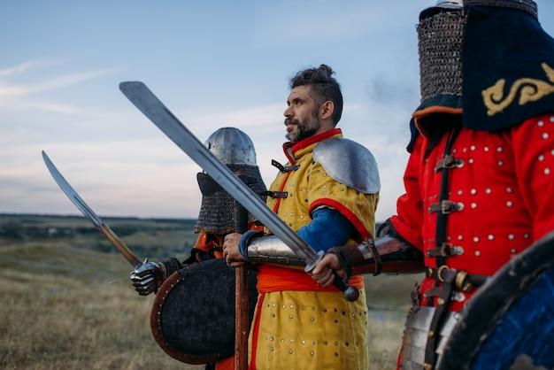 Middeleeuwse ridders met zwaarden en bijl poses in harnas, grote vechter. gepantserde oude krijgers in harnas poseren in het veld