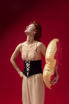 Middeleeuwse roodharige jonge vrouw als hertogin in zwart korset en nachtkleding die zich op rode muur met een zwemcirkel als doughnut bevindt. concept van vergelijking van tijdperken, moderniteit en renaissance.