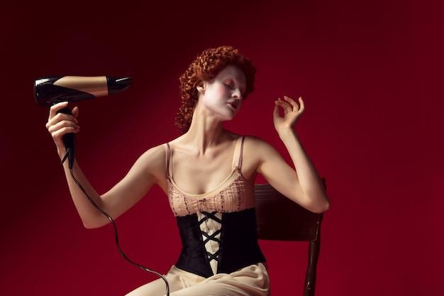 Middeleeuwse roodharige jonge vrouw als hertogin in zwart korset en nachtkleding zittend op de stoel op rode muur. haar haar doen met een droger. concept van vergelijking van tijdperken, moderniteit en renaissance.