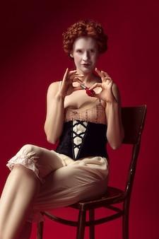Middeleeuwse roodharige jonge vrouw als hertogin in zwart korset en nachtkleding zittend op de stoel op rode ruimte