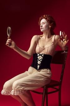 Middeleeuwse roodharige jonge vrouw als hertogin in zwart korset en nachtkleding zittend op een rode muur met een spiegel en een glas wijn. concept van vergelijking van tijdperken, moderniteit en renaissance.