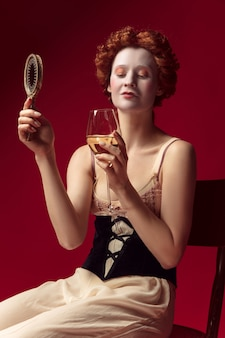 Middeleeuwse roodharige jonge vrouw als hertogin in zwart korset en nachtkleding, zittend op een rode ruimte met een spiegel en een glas wijn