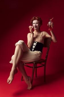Middeleeuwse roodharige jonge vrouw als hertogin in zwart korset en nachtkleding zittend op een stoel op rode muur met een drankje en een donut. concept van vergelijking van tijdperken, moderniteit en renaissance.
