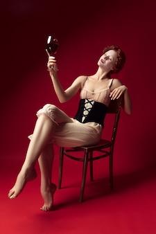 Middeleeuwse roodharige jonge vrouw als hertogin in zwart korset en nachtkleding zittend op een stoel op rode muur met een glas wijn. concept van vergelijking van tijdperken, moderniteit en renaissance.