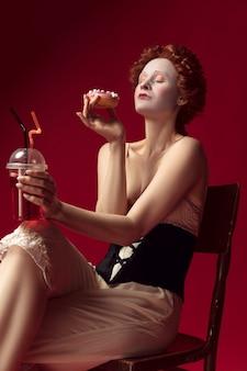 Middeleeuwse roodharige jonge vrouw als hertogin in zwart korset en nachtkleding zittend op een stoel op rode ruimte met een drankje en een donut