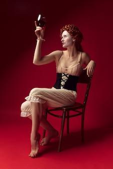 Middeleeuwse roodharige jonge vrouw als hertogin in zwart korset en nachtkleding zittend op een stoel op rode ruimte met een glas wijn