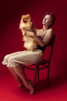 Middeleeuwse roodharige jonge vrouw als hertogin in zwart korset en nachtkleding, zittend op een stoel op rode ruimte met een kleine puppy of hond
