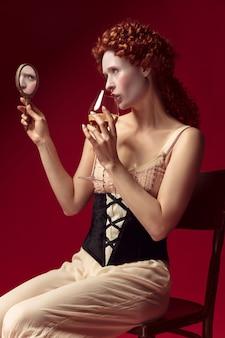 Middeleeuwse roodharige jonge vrouw als hertogin in zwart korset en nachtkleding zittend op rood