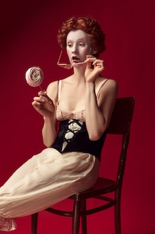 Middeleeuwse roodharige jonge vrouw als hertogin in zwart korset, zonnebril en nachtkleding zittend op een stoel op rode muur met een snoepje. concept van vergelijking van tijdperken, moderniteit en renaissance.