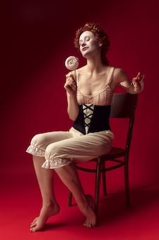 Middeleeuwse roodharige jonge vrouw als hertogin in zwart korset, zonnebril en nachtkleding zittend op een stoel op rode ruimte met een snoepje