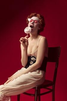 Middeleeuwse roodharige jonge vrouw als hertogin in zwart korset, zonnebril en nachtkleding