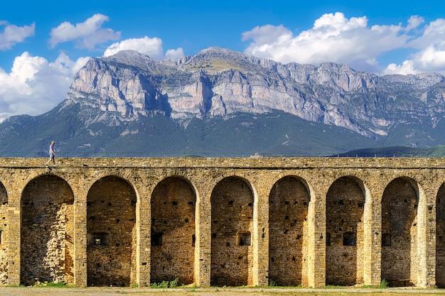 Middeleeuwse stenen bogen aquaduct fort met de pyreneeën berg op de achtergrond en wolken boven blauwe hemel. ainsa, spanje,