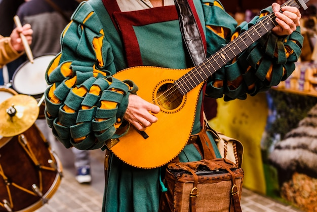 Middeleeuwse troubadour die een antieke gitaar speelt.
