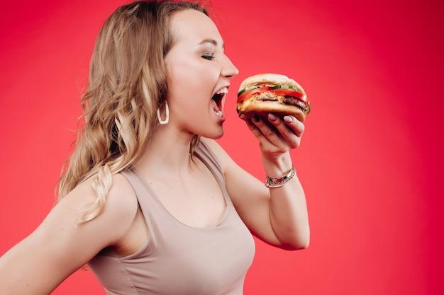 Middelgroot close-upportret van mooie jonge modevrouw die verse smakelijke sandwich bijt. portret van glimlachende schattige vrouw die zich voordeed terwijl ze geniet van het eten van fastfood in café