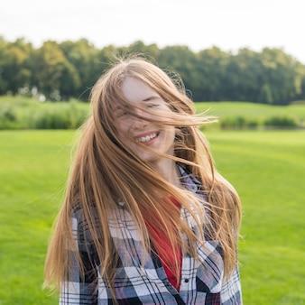 Middelgroot geschoten blondemeisje met het lange haar glimlachen