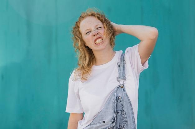 Middelgroot geschoten boos meisje met blauwe achtergrond