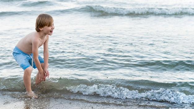 Middelgroot geschoten gelukkig kind aan zee