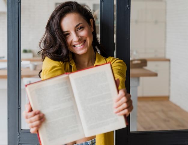 Middelgroot geschoten gelukkig meisje dat boek toont aan de camera