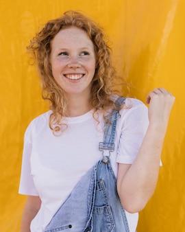 Middelgroot geschoten gelukkig meisje met gele achtergrond