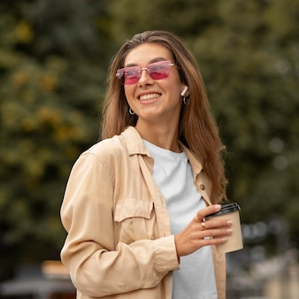 Middelgroot geschoten gelukkig meisje met koffie