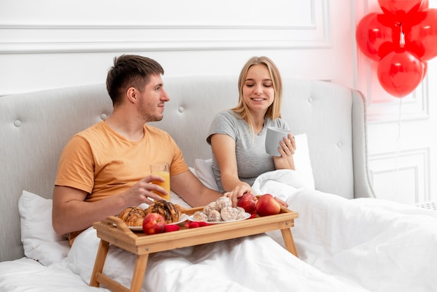 Middelgroot geschoten gelukkig paar dat ontbijt in slaapkamer heeft