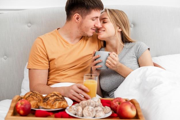 Middelgroot geschoten gelukkig paar met ontbijt en sap