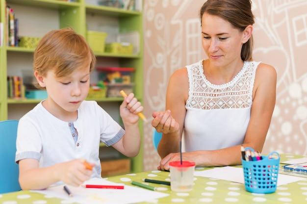 Middelgroot geschoten kind dat aan tafel tekent