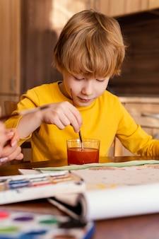Middelgroot geschoten kind dat aquarellen gebruikt