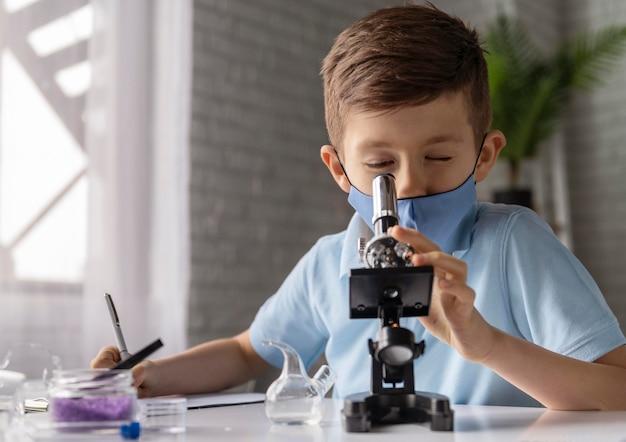 Middelgroot geschoten kind dat door microscoop kijkt