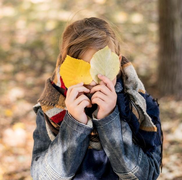 Middelgroot geschoten kind dat gezicht bedekt met bladeren