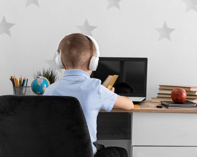 Middelgroot geschoten kind dat met laptop leert