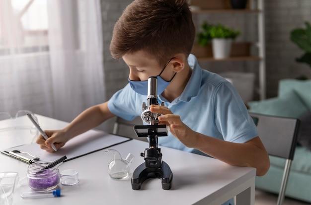 Middelgroot geschoten kind dat met microscoop leert
