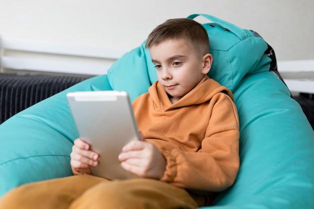Middelgroot geschoten kind dat met tablet studeert