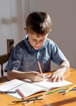 Middelgroot geschoten kind dat op notitieboekje schrijft Gratis Foto