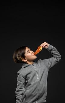 Middelgroot geschoten kind dat pizza met exemplaar-ruimte eet