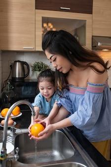 Middelgroot geschoten kind en moeder die sinaasappel wassen