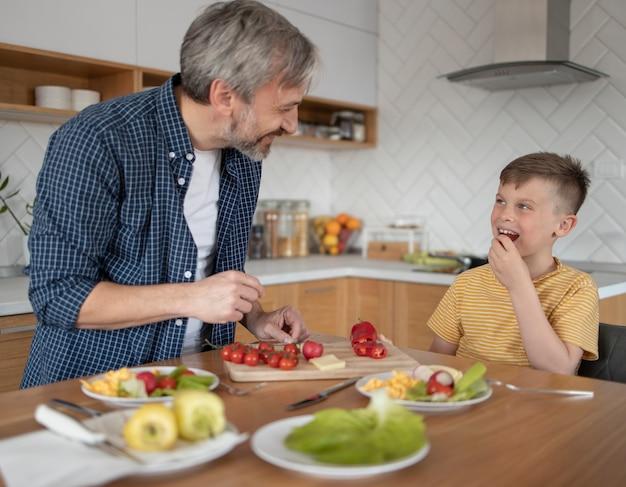 Middelgroot geschoten kind en ouder met eten Premium Foto