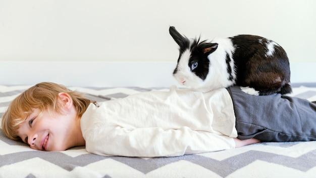 Middelgroot geschoten kind in bed met konijn