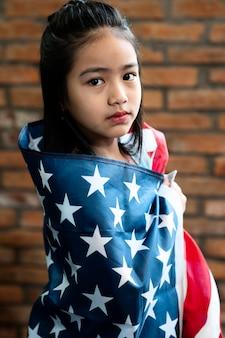Middelgroot geschoten meisje dat amerikaanse vlag houdt