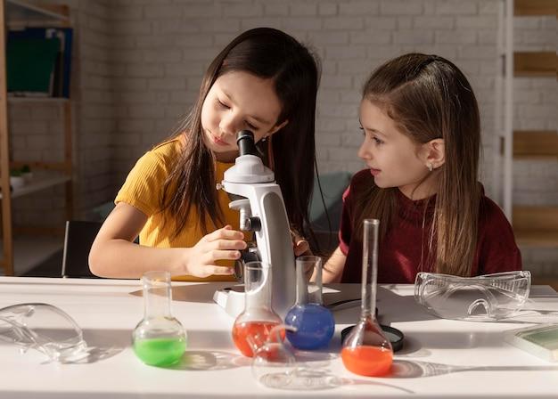 Middelgroot geschoten meisje dat door microscoop kijkt