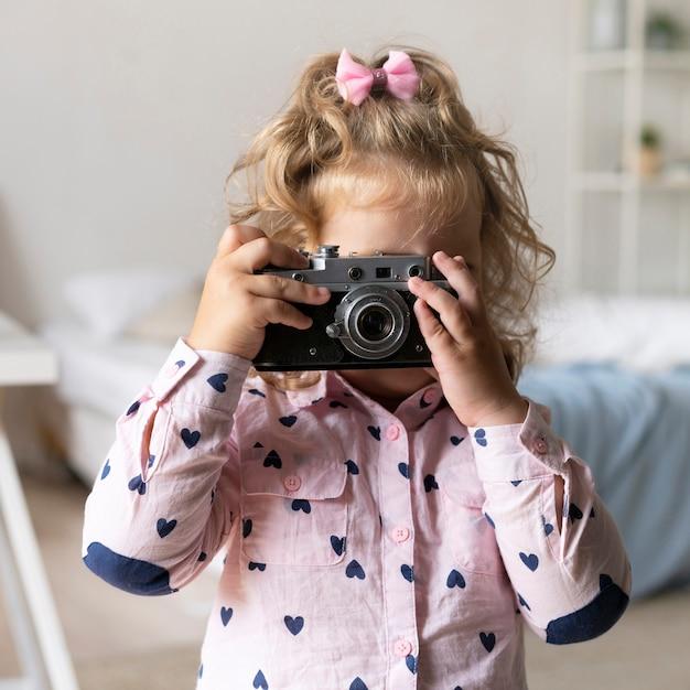 Middelgroot geschoten meisje dat foto's met camera neemt