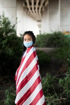 Middelgroot geschoten meisje dat gezichtsmasker draagt