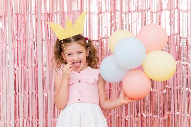Middelgroot geschoten meisje dat kleurrijke ballons houdt