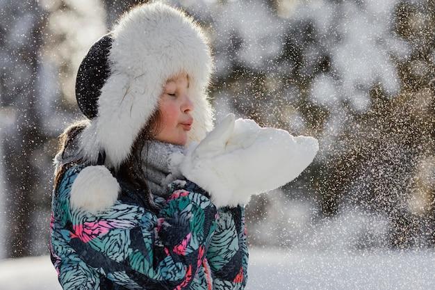 Middelgroot geschoten meisje dat met sneeuw speelt