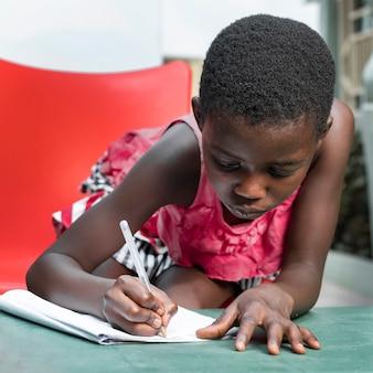 Middelgroot geschoten meisje dat op notitieboekje schrijft