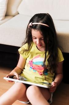 Middelgroot geschoten meisje die tablet op de vloer bekijken